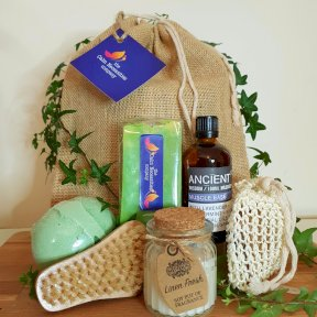 The Calm Necessities Company Aromatherapy for Him gift Set. Jute sack. Jojoba and Olive Oil artisan Handcrafted Soap, green. Muscle Ease Massage Oil with Lavender and peppermint 100ml brown glass bottle. Foot shaped Boar Hair and Hemu Wood Natural Scrubbi